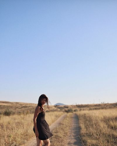 Woman standing on dirt road amidst grassy landscape against clear sky
