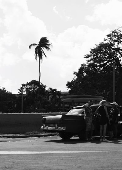 People sitting on road against sky