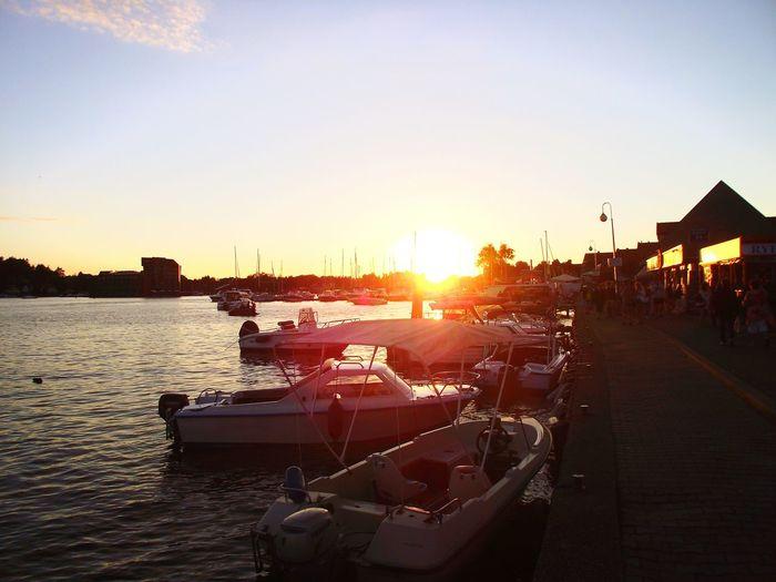 Zachód słońca nad promenadą w Mikołajkach Słońce Zachód Słońca. Woda Brzeg Promenada Mikołajki Mikolajki , Most , Mazury , Noc , Lodz , Widoki