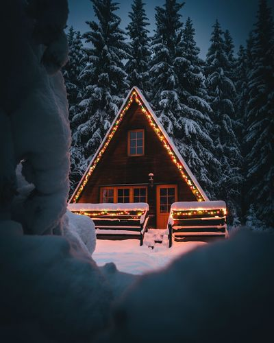 Illuminated house by building during winter