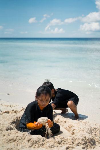 Siblings playing at beach against sky