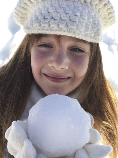 Close-Up Of Smiling Teenager Girl Holding Snowball During Winter