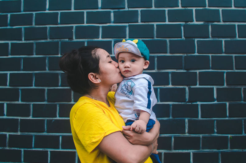 Lovely Love Loving The Street Photographer - 2019 EyeEm Awards People Portrait Togetherness Family Playing Baby Parent Wall Happy Happy People The Portraitist - 2019 EyeEm Awards Child Childhood Bonding Togetherness Crown Girls Females Smiling Yellow Babyhood Kissing 0-11 Months Baby Baby Boys Family Bonds