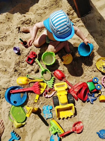 Directly above shot of boy playing with toys on sand at beach