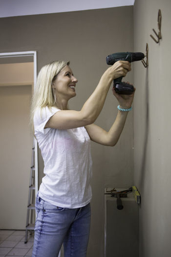 Woman Drilling Coat Hanger On Brown Wall