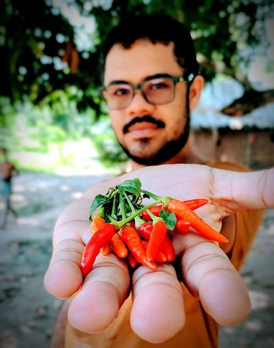 Close-up portrait of man holding red chili peppers