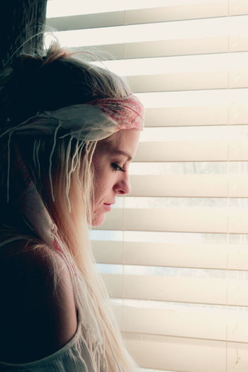 Thoughtful Beautiful Woman Standing Near Window