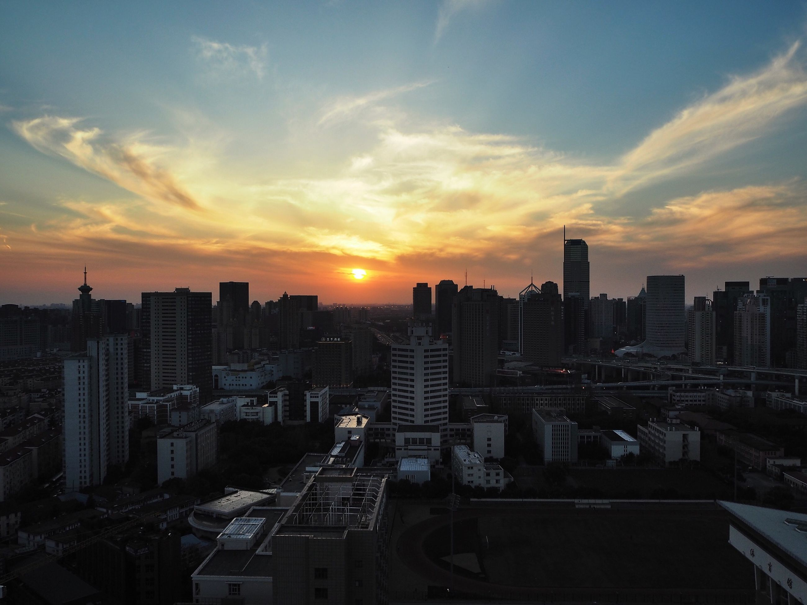 sunset, building exterior, city, cityscape, architecture, built structure, orange color, sky, high angle view, skyscraper, crowded, sun, residential district, city life, silhouette, residential building, cloud - sky, tower, urban skyline, sunlight