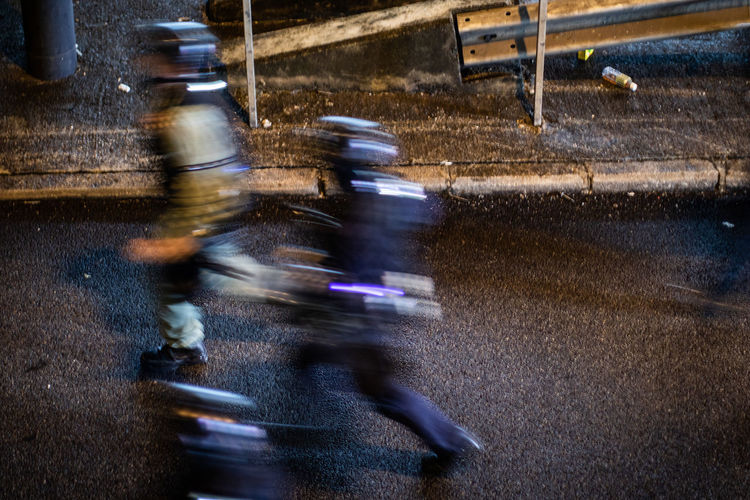 Blurred motion of person riding motorcycle on road in rain