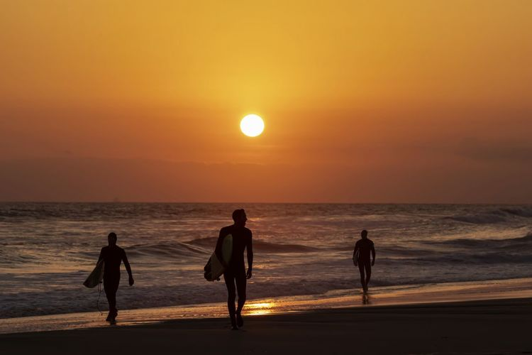silhouette of surfers walking on the beach during sunset Sunset Sky Sea Water Horizon Over Water Beauty In Nature Beach Horizon Scenics - Nature Orange Color Silhouette Real People Land Sun Men Lifestyles Idyllic Leisure Activity Nature Outdoors Surfers Huntington Beach Surfing Silhouettes Of People Orange County Southern California California