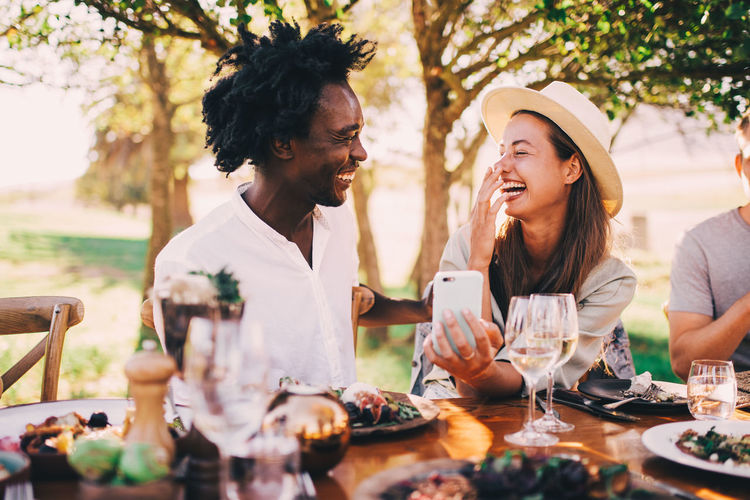 Table Happiness Real People Women Smiling Togetherness Two People Friendship Food And Drink Bonding Emotion Adult Sitting Lifestyles Young Adult Drink Females Enjoyment Casual Clothing Alcohol Glass Positive Emotion Phone Laughing Afro