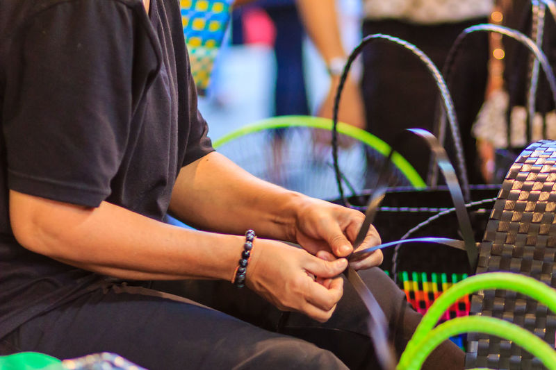 Close up hand of weaver during weaving basket made from plastic fiber. Weaver is weaving plastic basket show to the tourist in Bangkok, Thailand. Market Market Vendor Plastic Bag Weave Weaves Basket Basket Weave Chair Close-up Connection Day Focus On Foreground Human Hand Indoors  Marketplace Men Midsection People Plastic Plastic Baskets Real People Sitting Technology Two People Weaver Weaving Young Adult