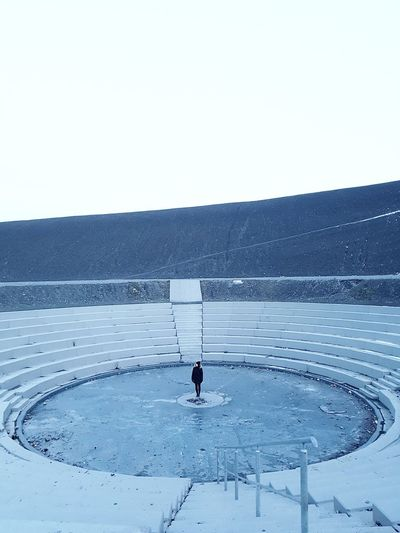 Iceland? One Person Winter Cold Temperature Frozen Water Female Model Lonliness Hill Amphitheater Abandoned Weathered Full Frame Adapted To The City Clear Sky Round Architecture Stairs Symmetry Minimalism Shades Of Grey Shades Of Blue Ice Real People The Architect - 2017 EyeEm Awards The Great Outdoors - 2017 EyeEm Awards Stories From The City