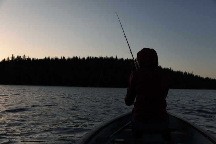 Rear view of man fishing in lake against sky during sunset