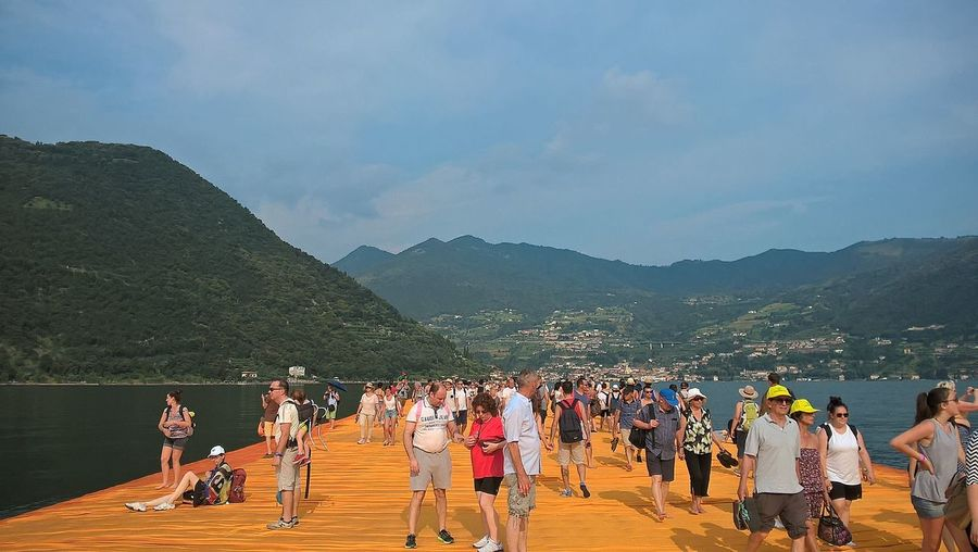 People on wooden pier over lake against sky