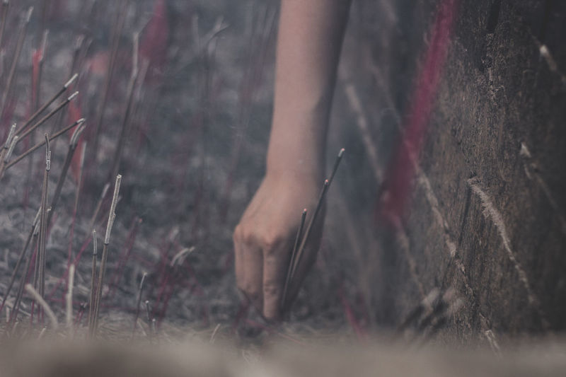 Cropped hand of woman placing lit incense stick in ash