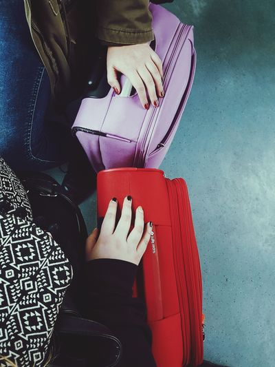 Low section of women sitting with suitcases