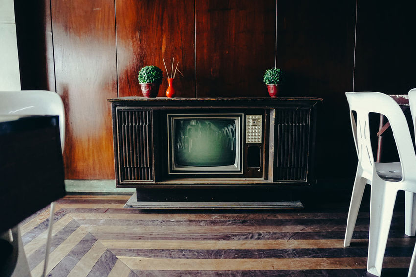 An old TV sits forgotten in a restaurant in Philippines 70s 80s Box Decor Messy Obsolete Old Technology Plants Retro Vintage Technology Wood Abandoned Cabinet Furniture Home Interior Indoors  No People Old Restaurant Technology Television Tv Tv Set Vintage Wood - Material