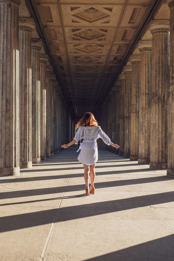 Rear view of young woman standing amidst columns