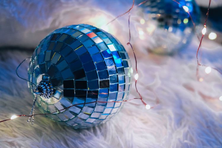 Two disco balls lying down on cozy blanket with christmas garland light. cozy home interior. home