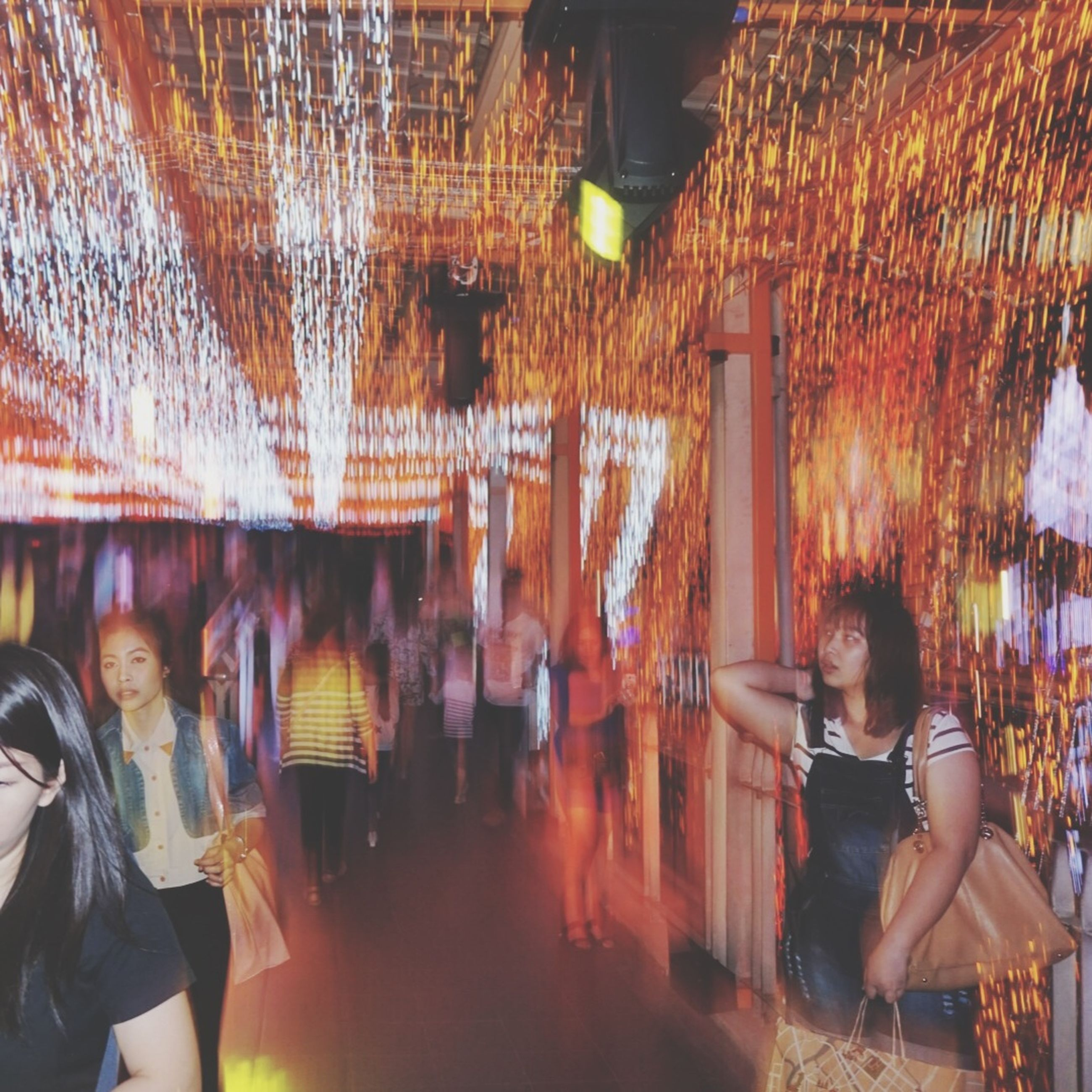 illuminated, indoors, lighting equipment, lifestyles, night, men, leisure activity, ceiling, person, lantern, standing, hanging, architecture, retail, casual clothing, built structure, rear view, large group of people