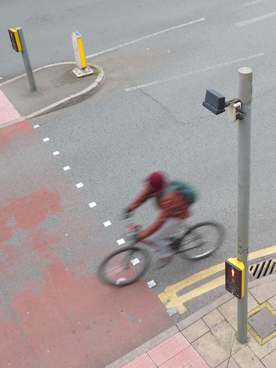Blurred motion of person riding bicycle on road