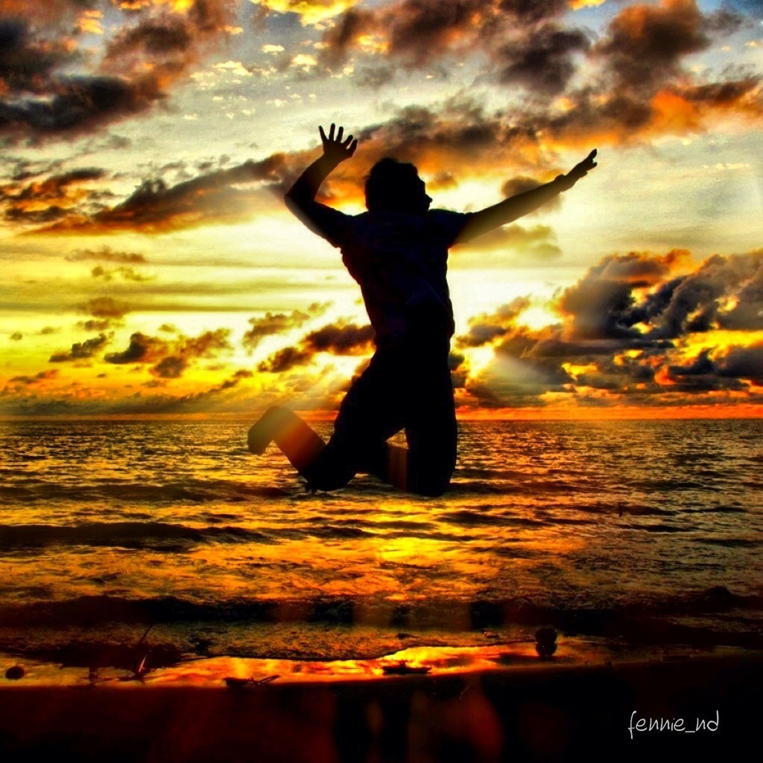 sunset, sky, lifestyles, leisure activity, sea, silhouette, cloud - sky, beach, orange color, full length, water, standing, dramatic sky, arms raised, scenics, person, horizon over water, beauty in nature