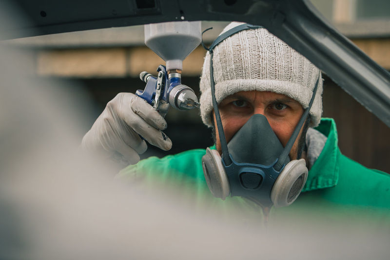 Close-up portrait of man painting while wearing gas mask
