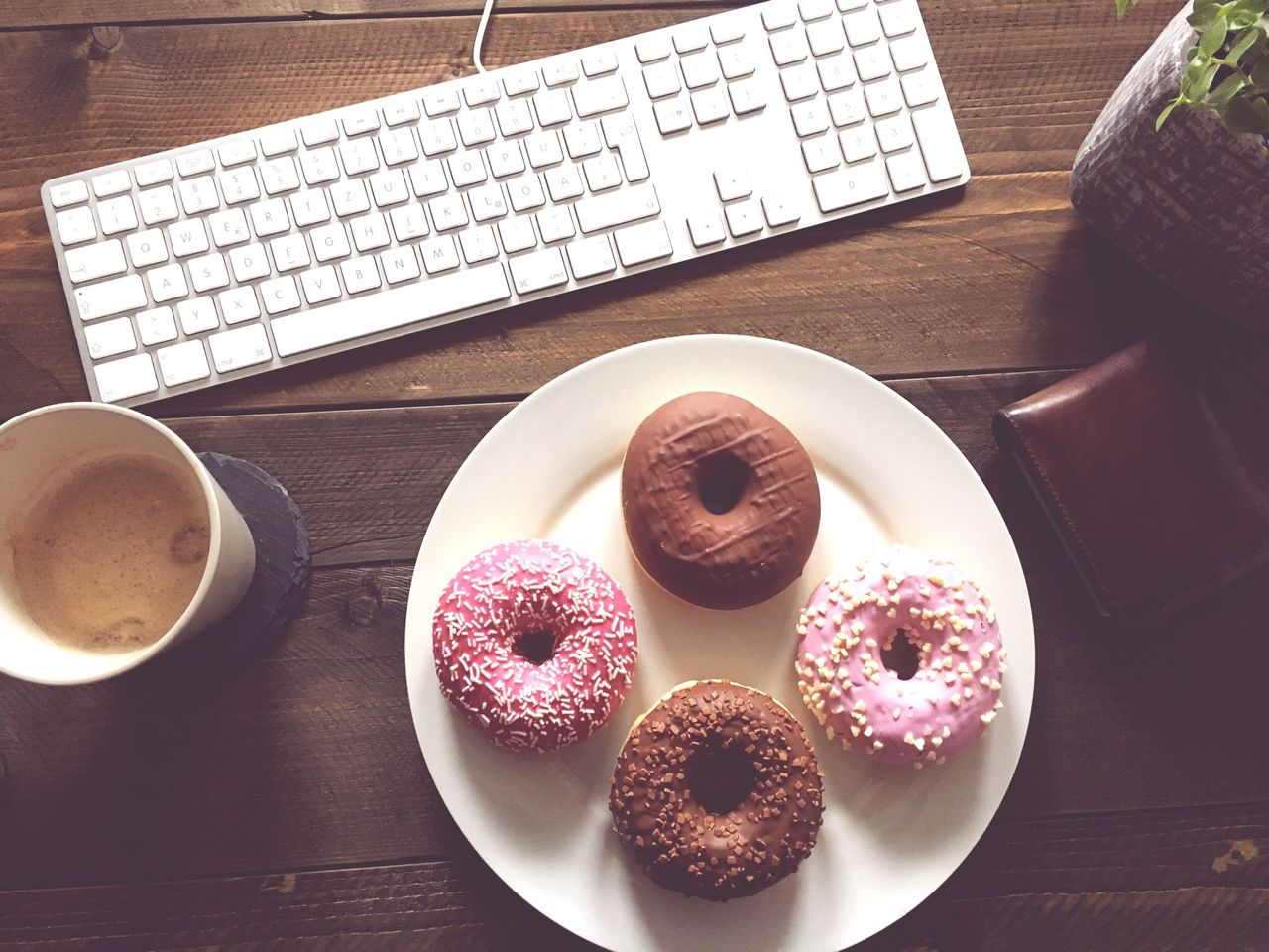 High Angle View Of Donuts In Plate By Keyboard On Wooden Table