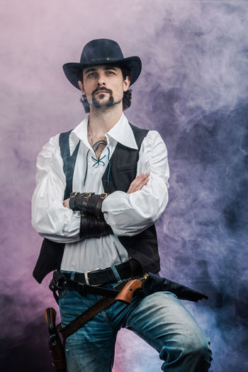 Handsome young man. This is an American cowboy. A vow to a white shirt, brown waistcoat and blue jeans. Black shoes on the feet. Carries a shtyapa, on a belt two pistols. The hair is of medium length; on the face is a beard and mustache. Authentic photo. Culture of America. Cowboy Wild West America American Gun National Authentic Moments Lifestyles Lifestyle One Person Candid Authentic Real People Three Quarter Length Smoke - Physical Structure Facial Hair Front View Beard Hat Clothing Casual Clothing Mid Adult Men Holding Mid Adult Men