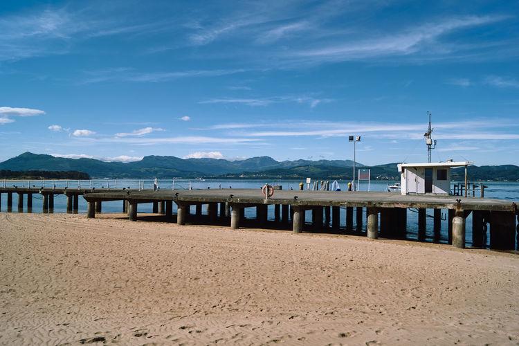 Pier on beach against sky