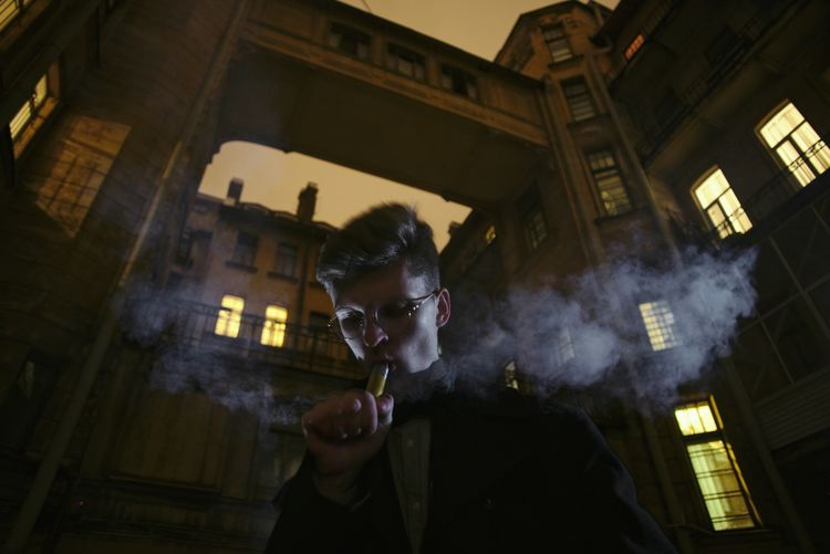 Low Angle View Of Man Smoking Electronic Cigarette Against Illuminated Building At Dusk