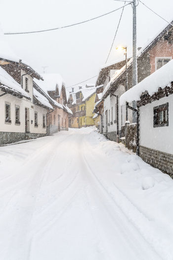Snow covered road amidst houses and buildings in city
