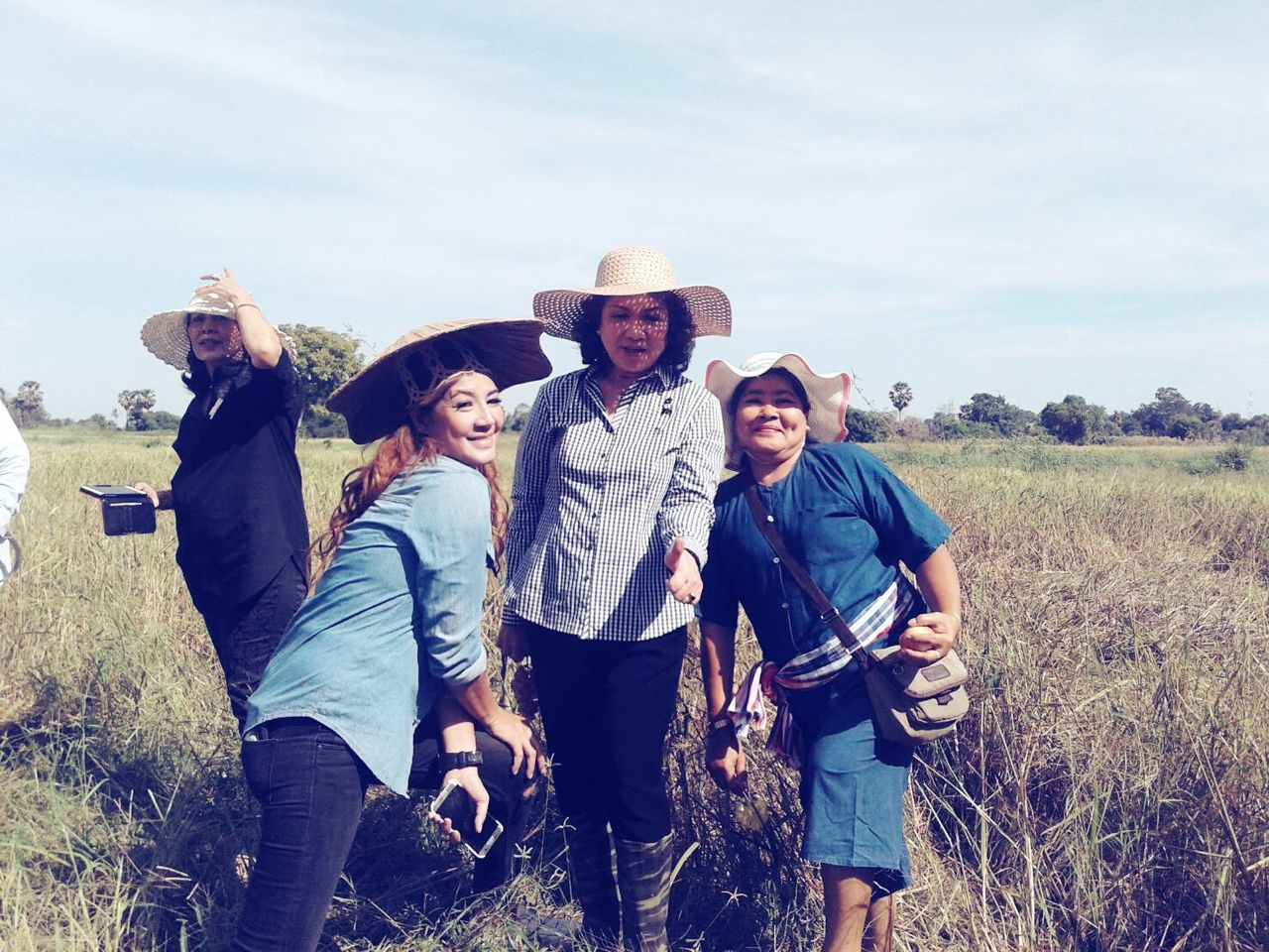 hat, casual clothing, friendship, togetherness, young adult, portrait, happiness, cowboy hat, real people, looking at camera, smiling, leisure activity, young women, field, outdoors, front view, day, standing, young men, lifestyles, sky, cheerful, nature, group of people, grass, landscape, adventure, bonding, men, wild west, adult, people