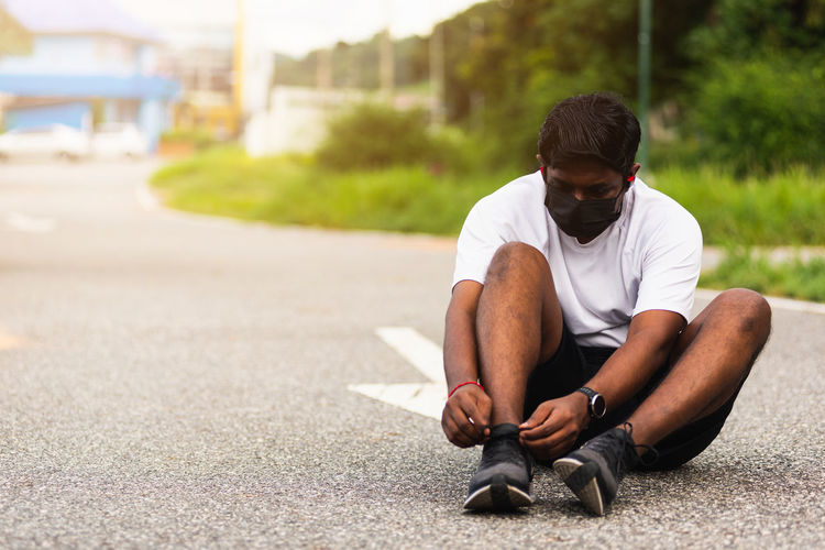 Young man sitting on road