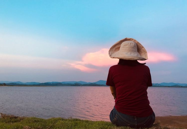 Asian woman sitting for looking the lake on sunset twilight sky One Person Sky Water Hat Beauty In Nature Real People Beach Rear View Women Cloud - Sky Land Three Quarter Length Standing Sea Scenics - Nature Leisure Activity Outdoors Sunset Nature Lifestyles
