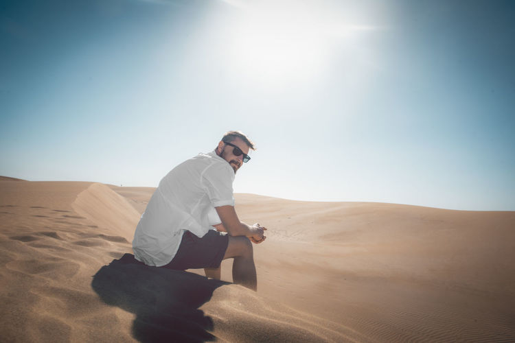 Young man sitting on sand dune in desert