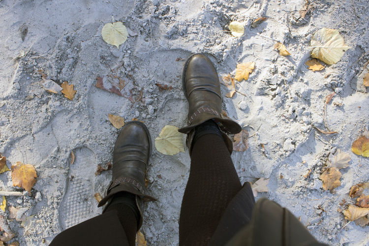 Low Section Shoe Personal Perspective Human Leg Human Body Part Body Part One Person Real People High Angle View Standing Outdoors Unrecognizable Person Boot Footpath Sand Leaves