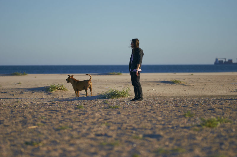 Woman with dog standing at beach
