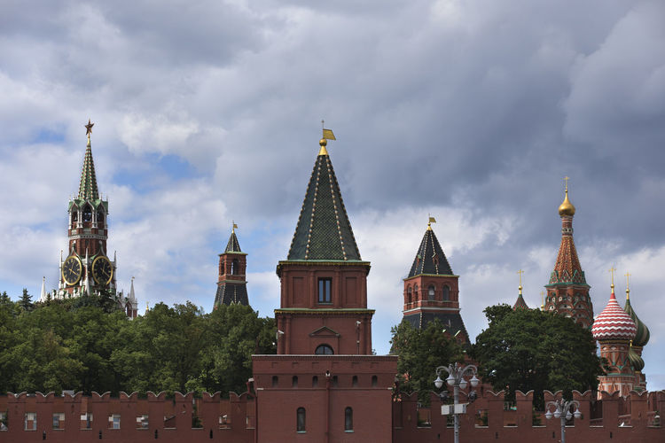 Russia, Moscow, view on Kremlin towers on against dramatic cloudy sky. Architecture Building Exterior Built Structure Cloud - Sky Day Low Angle View Moscow; Kremlin; Russia; Architecture; Cathedrals; City; Landmarks; Urban; Travel; Locations; Destination; Cityscape; Tower; Wall. Nature No People Outdoors Place Of Worship Religion Sky Spirituality Travel Destinations Tree