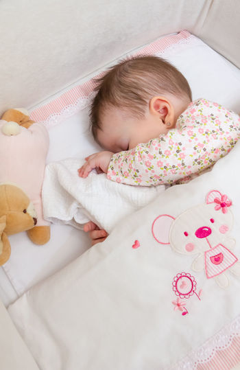 High angle view of baby girl sleeping in crib at home