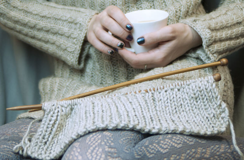 a young woman knits on the spokes and drinks coffee Cozy Hands Home Knitted Sweater Openwork Text Background Woman Coffee Time Copy Space Craft Gray Hand Holding Hot Drink Hot Drink, Cozy Hot Drinks Human Hand Indoors  Keep Warm Lace Lace - Textile Openwork Textile Winter Evening, Outside Type Of Tree Wool