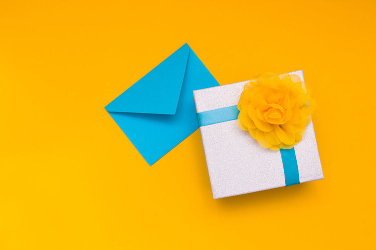 High angle view of box with envelop over yellow background
