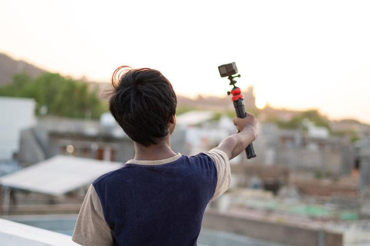 Rear view of man photographing food against sky