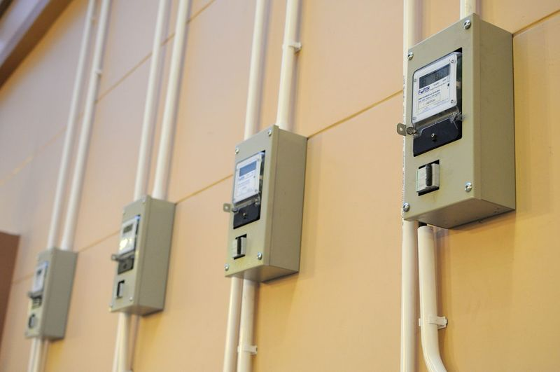 Low angle view of electric meter boxes on wall