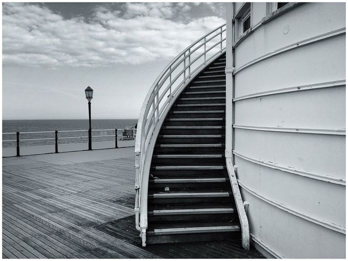 Steps by sea against cloudy sky