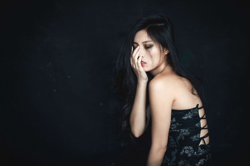 Crying woman posing against black background