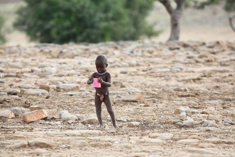 Grootberg, Namibia African Child Ancient Civilization Beauty In Nature Casual Clothing Child Playing Childhood Field Focus On Foreground Grootberg Happiness Himba Himba Tribe Innocence Of Youth Leisure Activity Lifestyles Namibia Peaceful Showcase June Tranquility