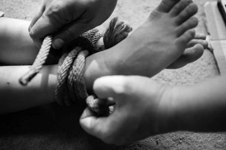 Cropped hands of man tying woman legs on floor