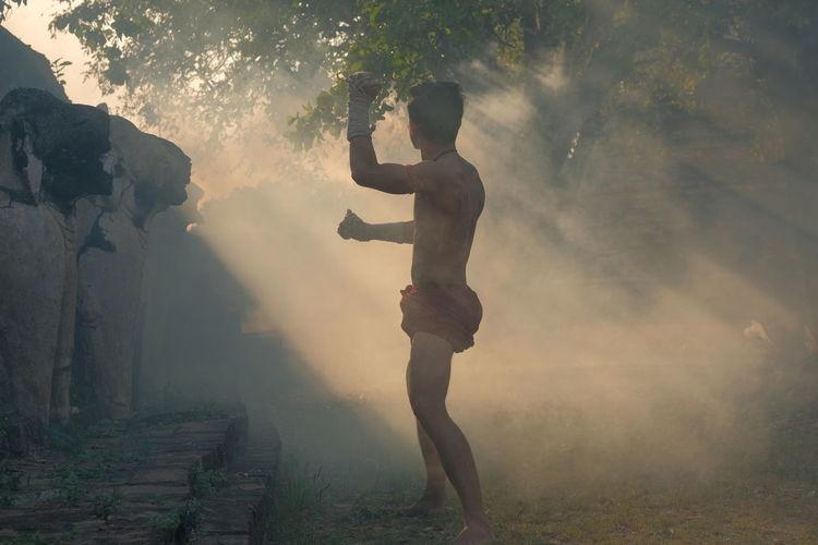 Side view of shirtless man exercising on land